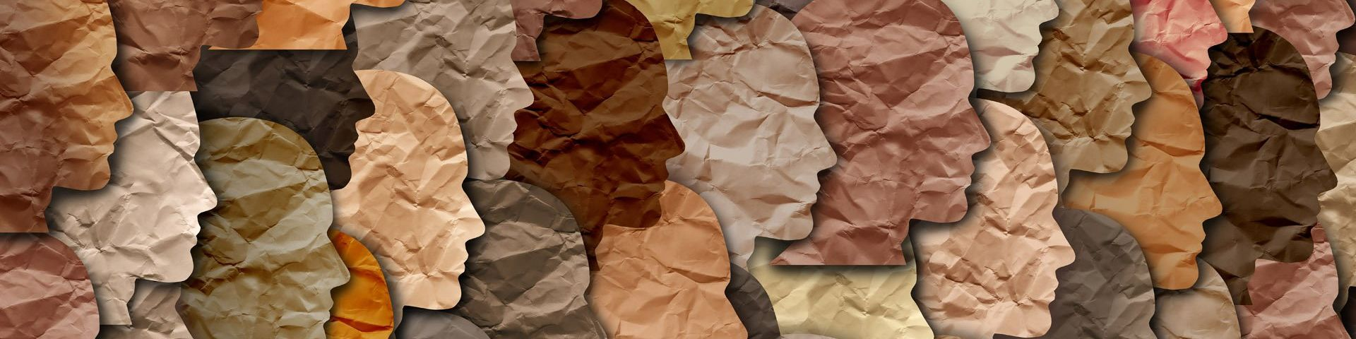 Featureless, slightly crumpled paper faces of all different skin tones, facing right and overlaid onto each other in a collage style